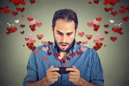 Retrato joven hombre sorprendido guapo envío de la recepción de mensajes de texto SMS de amor en el teléfono móvil con corazones rojos volando hacia arriba sobre fondo gris de la pared. Las emociones humanas