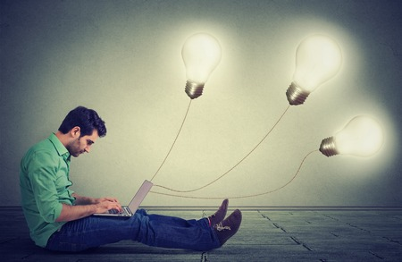 plugged in': Side profile man sitting on floor using a laptop with many light bulbs plugged in it