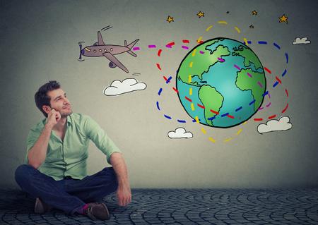 Junger stattlicher Mann, Reisende auf dem Boden auf der ganzen Welt über eine erstaunliche Reise zu denken sitzen Standard-Bild