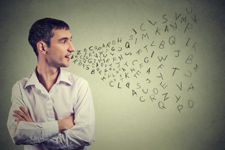 Profilo laterale uomo che parla con le lettere dell'alfabeto che esce dalla sua bocca. Comunicazione, informazione, concetto di intelligenza