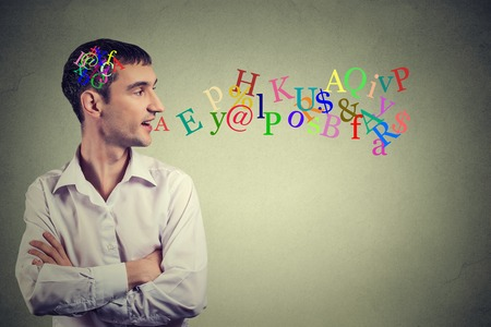 intelligence: Side view portrait man talking with alphabet letters in his head and coming out of open mouth isolated on gray wall background. Human face expressions, emotions. Communication, intelligence concept