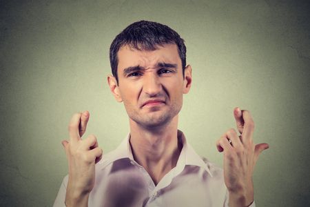 crossing fingers: Young desperate man making a wish crossing fingers isolated on gray wall background Stock Photo