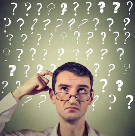 seeks: Portrait confused thinking young man in glasses bewildered scratching his head seeks a solution looking up at many question marks isolated on gray wall background. Human face expression