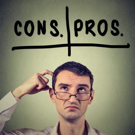cons: pros and cons, for and against argument concept. Young business man with glasses looking up deciding isolated on gray wall background. Face expression, emotion, feeling, perception, vision