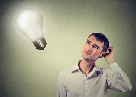 Closeup handsome concerned man thinks looking up at bright light bulb isolated on gray wall background. Idea, business, education and people concept. Human face expression