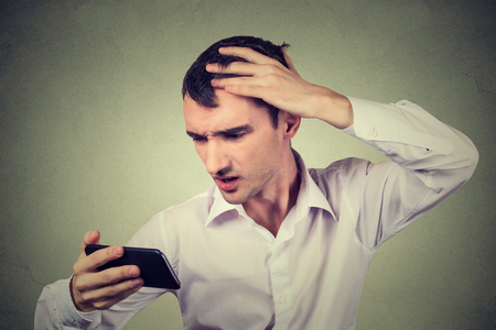 thinning: Closeup portrait, shocked man feeling head, surprised he is losing hair, receding hairline, bad news isolated on gray wall background. Negative facial expressions, emotion feeling Stock Photo