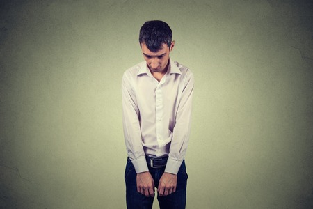 accused: sad lonely young man looking down has no energy motivation in life depressed isolated on gray wall background Stock Photo
