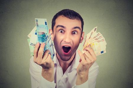 dinero euros: hombre joven feliz del retrato con el dinero de billetes de euro celebra el éxito de éxtasis gritando aislados sobre fondo gris. Logro libertad financiera
