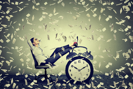 falling: Happy young business woman relaxing sitting in her office under money rain making money dollar bills cash falling down. Stress free time management good earnings profit concept Stock Photo