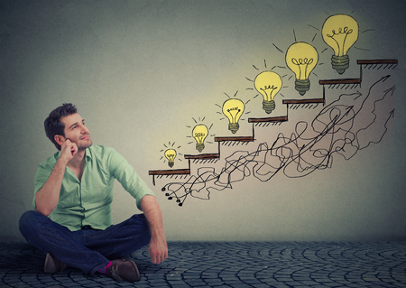 growing business: Happy man sitting on a floor in his office dreaming of business education success, promotion, company growth isolated gray wall texture background. Handsome guy looking up at growing up light bulbs