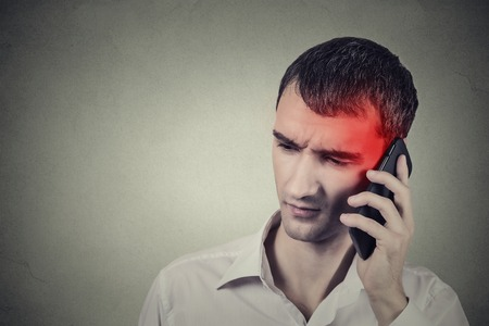 telephone call: Man on the phone with headache. Upset unhappy guy talking on a phone isolated grey wall background. Negative human emotion face expression feeling life reaction. Cellular mobile radiation concept