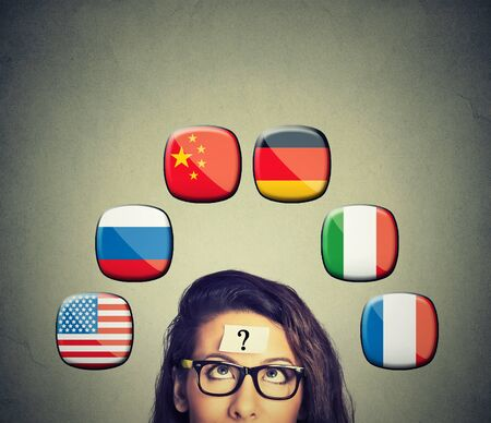 Work and travel immigration opportunity concept. Foreign language studying process. Woman with question mark and icons of international flags above head isolated on gray wall background.