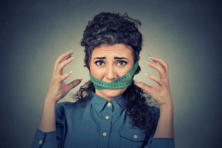 obsessed: Diet restriction and stress concept. Portrait of young frustrated woman with a green measuring tape around her mouth isolated on gray wall background. Face expression emotion