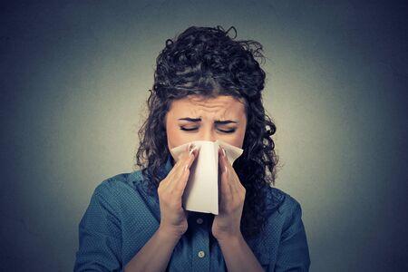 nariz: mujer Retrato del primer estornudar en un pañuelo de papel que sopla su nariz que moquea Foto de archivo