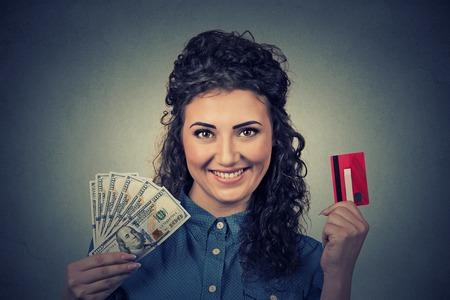 cash money: Joven mujer de compras de cartera que muestra la tarjeta de crédito y dinero en efectivo en dólares billetes de banco facturas Foto de archivo