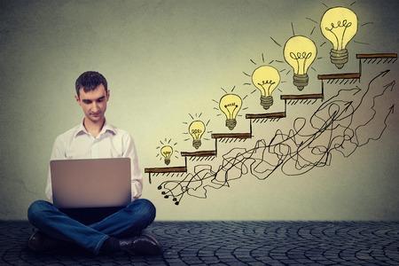 incremento: Empresario joven feliz que trabaja en la computadora que se sienta en un piso en su oficina con éxito en tráfico creciente del Web site de Internet. Promoción, concepto de crecimiento de la empresa. Aislado en fondo gris de la pared