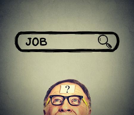 Hombre mayor en los vidrios que miran hacia arriba en busca de un trabajo aislado en el fondo de la pared gris. concepto de mercado de trabajo Empleo Foto de archivo
