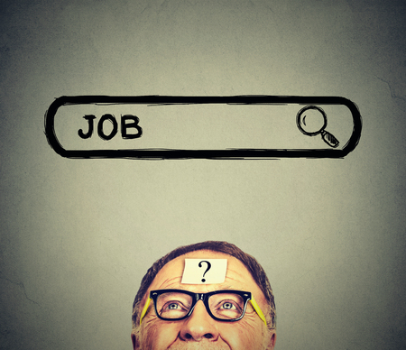 Senior man in glasses looking up searching for a job isolated on gray wall background. Employment job market concept