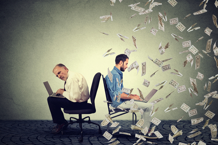 Employee compensation economy concept. Senior man working on laptop sitting next to young entrepreneur guy using computer under money rain. Pay difference concept. Stock Photo