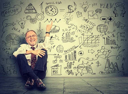 Happy senior business man elderly entrepreneur teacher sitting on a floor pointing at new project calculations on gray wall background