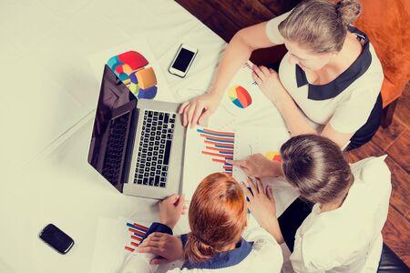 Trois femmes d'affaires consultant en investissement société analysant déclaration annuelle du bilan de rapport financier travaillant avec des documents graphiques. Marché boursier, bureau, impôts, concept. Mains avec cartes papiers