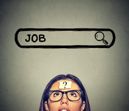 Headshot młoda kobieta w okularach myślących, poszukujących nowej pracy samodzielnie na szarym tle ściany Zdjęcie Seryjne