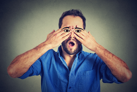 claustrophobia: Surprised handsome man with eyes painted on his hands
