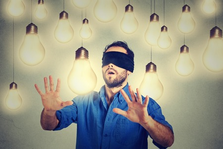 Blindfolded young man walking through light bulbs searching for bright idea Foto de archivo