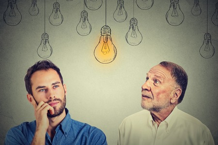 pensive man: Cognitive skills concept, old man vs young person. Senior man and young guy looking at bright light bulb isolated on gray wall background