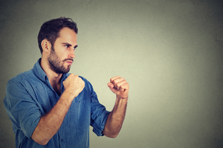 enrage: Angry young man clenching his fists