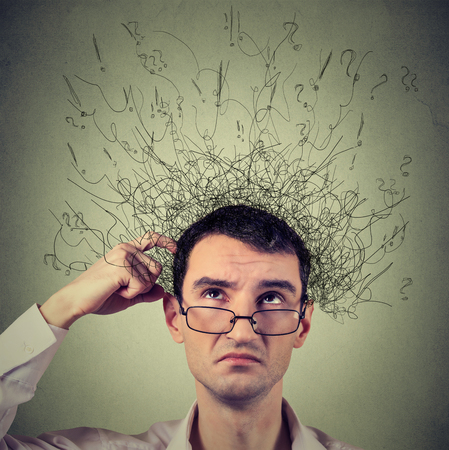 Closeup portrait young man scratching head, thinking daydreaming with brain melting into many lines question marks looking up isolated on gray background. Human facial expression emotion feeling sign Stock Photo