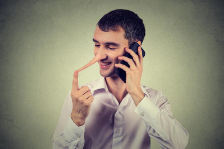 character traits: Liar customer service representative. Happy young man with long nose talking on mobile phone isolated on gray wall background. Liar concept. Human face expressions emotion feelings, character traits Stock Photo