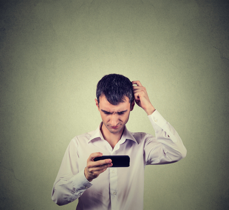 face to face: Closeup portrait perplexed young man looking at smart phone seeing bad news or photos with confused emotion on his face isolated on gray wall background. Human reaction, expression