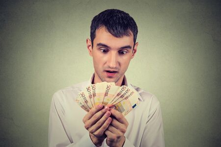 avarice: Young greedy business man counting money
