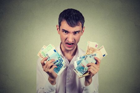 billets euros: homme Greedy avec des billets de banque en euros factures isolé sur gris fond mur