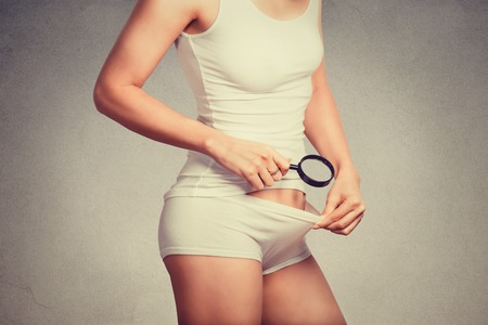Young attractive slim woman looking with a magnifying glass on her pubic hair on the crotch isolated on gray wall background. Women health hygiene concept. Skin body care Stock Photo