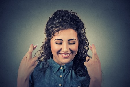 hispanic woman: Closeup portrait hopeful beautiful woman crossing her fingers, eyes closed, hoping, asking best isolated on gray wall background. Human face expression, emotions, feeling attitude reaction