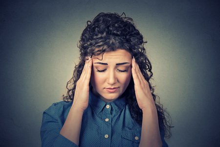 woman headache: Closeup sad young woman with worried stressed face expression having headache isolated on gray wall background. Human emotions, mental health concept Stock Photo