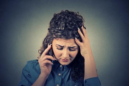 Retrato infeliz mujer joven hablando por teléfono móvil mirando hacia abajo. Expresión del rostro humano, la emoción, la reacción de malas noticias Foto de archivo