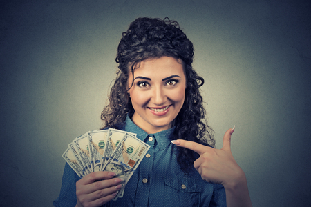 cash back: Closeup portrait super happy excited successful young business woman holding money dollar bills in hand isolated on gray background. Positive emotion facial expression feeling. Financial reward