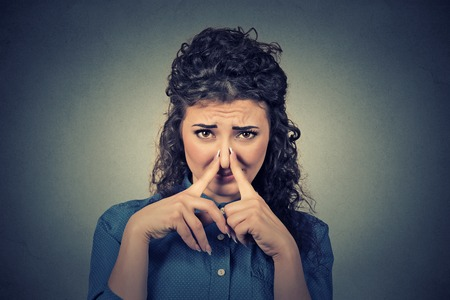 Closeup portrait young woman pinches her nose with fingers looks with disgust something stinks bad smell isolated on gray wall background. Human face expression body language reaction Stock Photo
