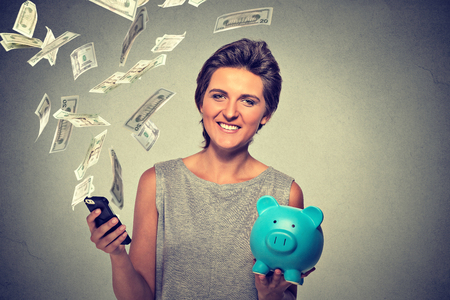 cellular: Technology online banking money transfer, e-commerce. Happy woman with piggy bank and smart phone dollar banknotes bills flying away isolated gray background. Online income business concept
