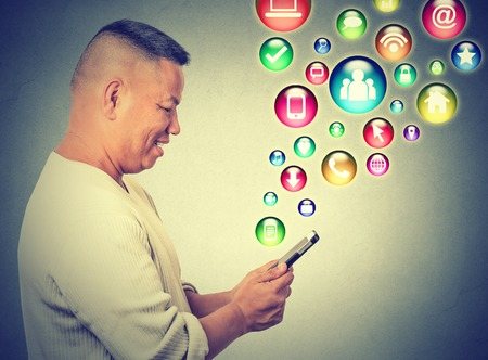 application: Communication technology mobile phone high tech concept. Side profile happy man using texting on smartphone social media application icons flying out of cellphone isolated grey background. Data plan Stock Photo