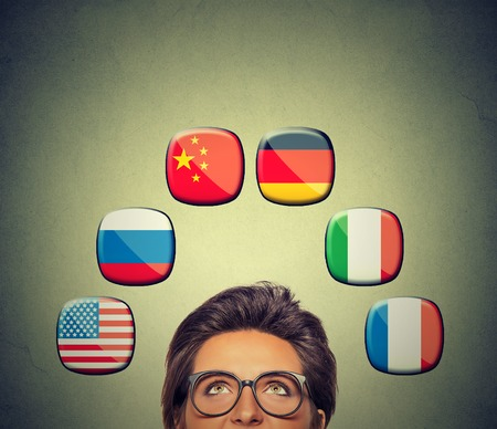 foreign country: Work and travel opportunity concept. Foreign language studying process. Woman in glasses looking up at icons of international flags above head isolated on gray wall background. Stock Photo