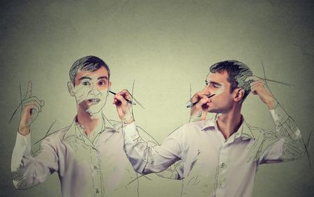 Cree usted mismo concepto. Buen hombre joven que busca un dibujo, boceto de sí mismo en el fondo gris de la pared. expresiones faciales humanas, la creatividad