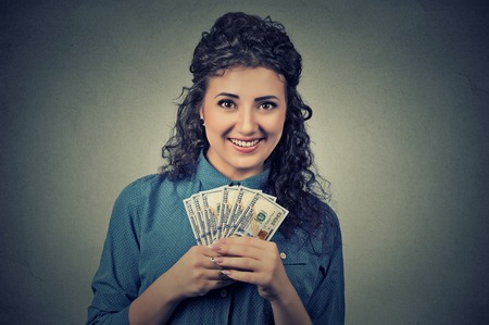 financial reward: Closeup portrait happy excited successful young business woman holding money dollar bills in hand isolated on grey wall background. Positive emotion facial expression feeling. Financial reward Stock Photo