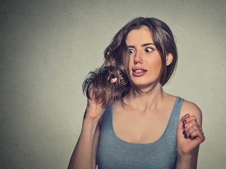 クローズ アップ イライラ ショックを受けた若い女性彼女の新しい髪のカットに不満に気づいた枝毛は、灰色の背景に分離されました。人間の顔の 写真素材