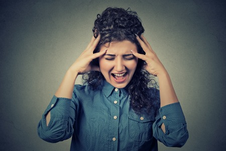 tantrum: Closeup portrait stressed frustrated young woman yelling screaming having temper tantrum isolated on gray wall background. Negative human emotion facial expression reaction attitude