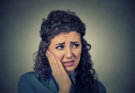 negative emotion: Closeup portrait young woman with sensitive toothache crown problem about to cry from pain touching outside mouth with hand isolated on gray background. Negative emotion face expression feeling