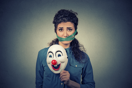 obsessed: Diet restriction and stress concept. Portrait of young sad woman with clown mask and measuring tape around her mouth isolated on gray wall background. Unhappy face expression emotion